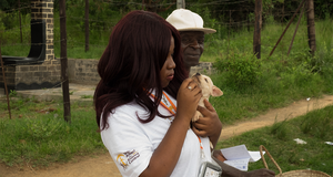 Woman holding puppy during vaccination campaign.
