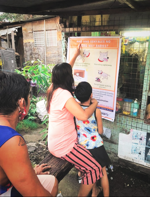A mother and child read a GARC rabies awareness poster as they wait in line at a local shop.